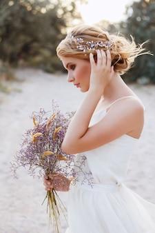 ビーチで風通しの良い白いドレスを着た花嫁。夏の結婚式の花嫁の髪型。背景をぼかし。
