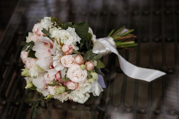 鏡面にブライダルブーケ。白いリボンのウェディングブーケ。クラシックなスタイルの結婚式。花屋