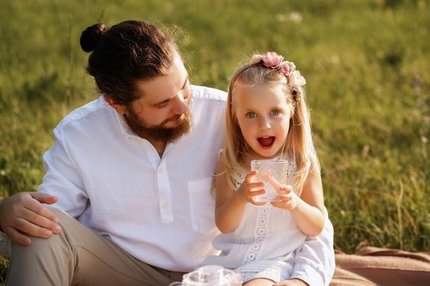 父と娘の夏のピクニック。女の子はグラスからジュースを飲むし、幸せ
