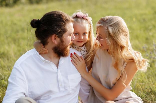 Маленькая девочка обнимает своих родителей. счастье. летний пикник