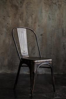 暗い空間に背を向けた黒い鉄の椅子。インテリアの詳細