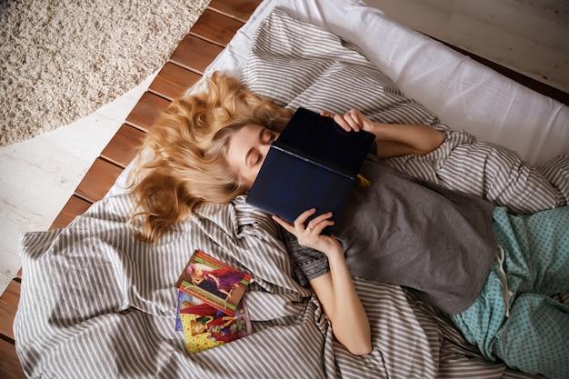 ブロンドの女の子はベッドで読みます。怠惰なおはようございます。パジャマ。家に
