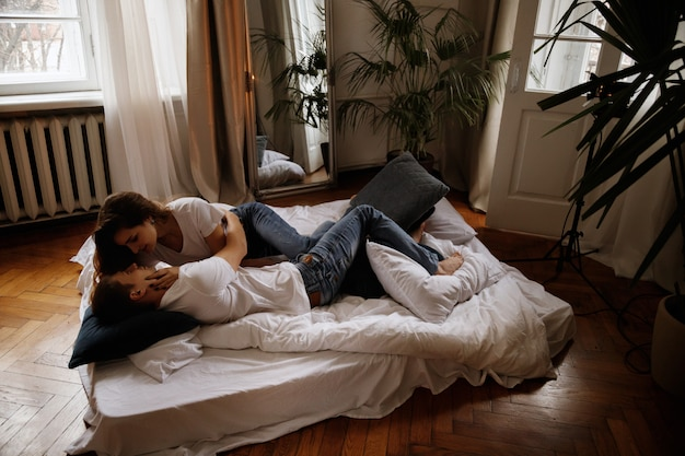 Влюбленная пара в спальне на кровати у себя дома. суббота. темное фото