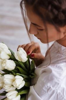 チューリップの花束と美しい若い女性。クローズアップの春の肖像画。太陽光線と白い花の花束とインテリアで幸せでロマンチックな女性。女の子と白いシャツ