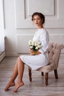 ヨーロッパの暗い髪の少女は窓際の白いスタジオに立って、白いチューリップの花束を保持しています。