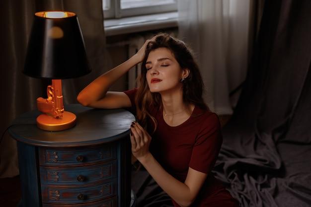 Портрет модели в бордовом платье вечером в темной студии