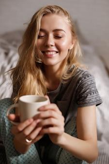 ブロンドは朝のコーヒーのカップを保持しています