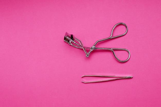 Пинцет и бигуди для ресниц на розовом фоне. ухаживать за ресницами и бровями