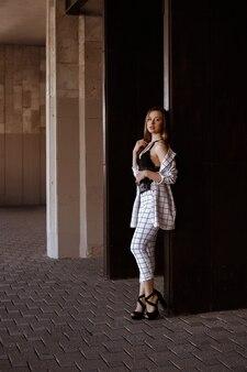 黒のウエストバッグと白のスーツのフルレングスモデル。夏の都会的なスタイル