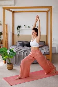 Молодая женщина, занимаясь йогой дома. останься дома. утренняя гимнастика и медитация.
