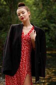 の背景に魅力的な服の若い女性。パーティーのイメージ。赤いドレス、黒いジャケット。イブニングメイク