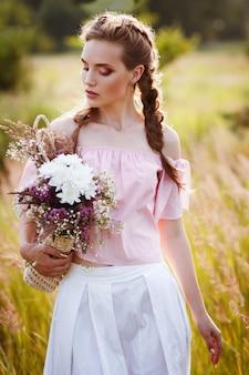 野生の花の花束を持つエレガントな女の子