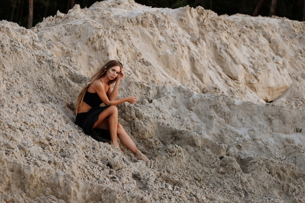 夏の砂浜で黒い服を着た女の子。ドレッドロックス