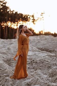 夏の砂浜でシースルーのロングドレスを着た日焼け少女