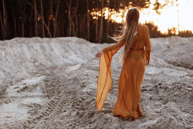 夕暮れの砂浜で水着と透明な茶色のドレスの女の子