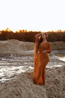 夕暮れの夏の砂浜で透明な岬に長い髪の少女