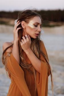 ドレッドヘアと砂の夕日で夏のゴールドのメイクアップで日焼けしたモデル