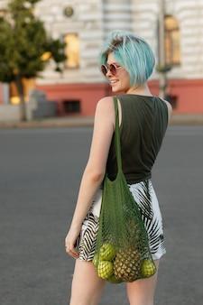 メガネの色とりどりの髪と街の夕方には果物の透明な袋を持つ少女。ショッピングバッグ