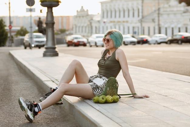 市内の夏に休んでいる果物の袋を持つスポーツ少女
