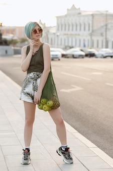 Девушка с синими волосами в очках и сумке с фруктами летом