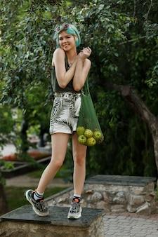 Симпатичная девушка с синими волосами и мешком фруктов на зеленом пространстве летом