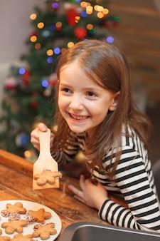 Веселая девушка готовит сладкое печенье на кухне