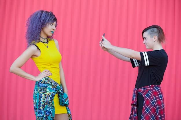 Молодые межрасовые молодые подружки фотографируют друг друга