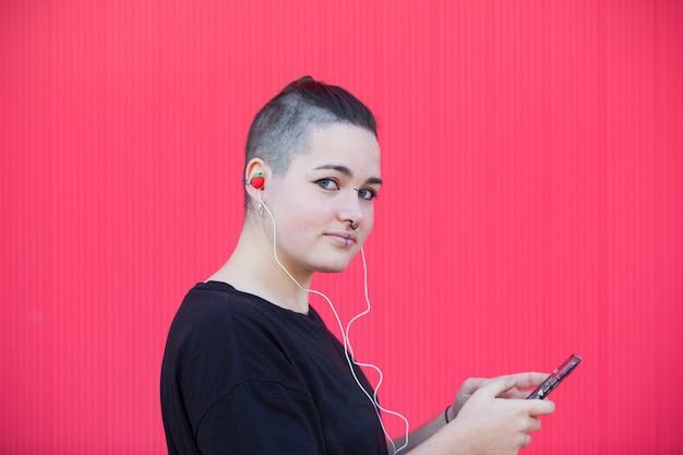 Андрогинный подросток слушает музыку в розовых наушниках
