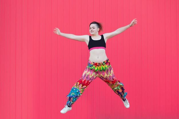 Андрогинная женщина прыгает с разноцветной одеждой на розовой стене