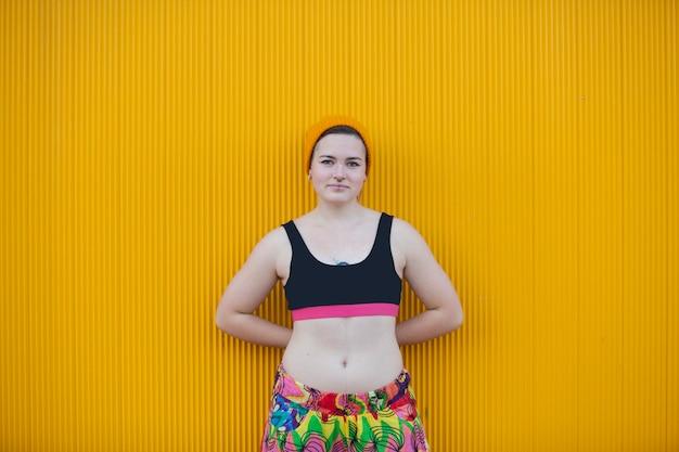 Подростковая андрогинная женщина на желтой стене