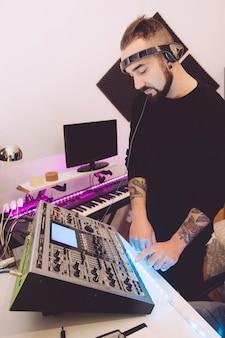 Музыкальный техник микширует треки в своей студии с наушниками