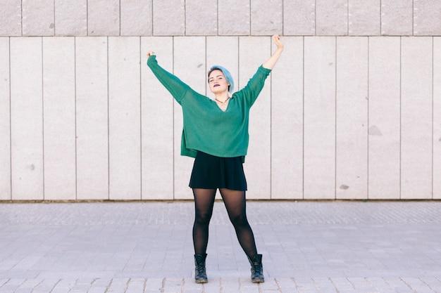 Веселая андрогинная девушка с голубыми волосами и широко открытыми руками