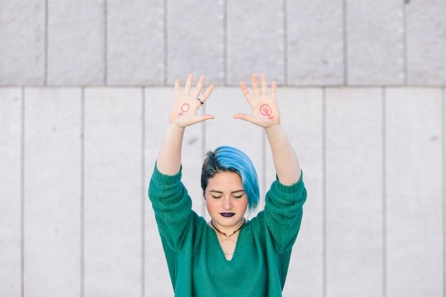 Сильная молодая женщина борется за гендерное равенство с феминистским символом на обеих руках