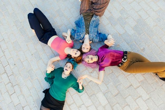 地面に横たわって一緒に分離された手を繋いでいる若い女性のグループ