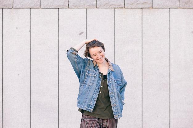 Веселая молодая девушка стоит на улице с счастья и позитивного отношения