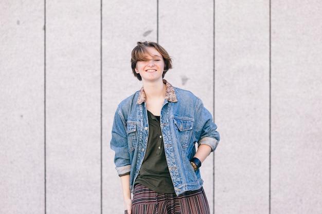 Веселая молодая девушка с короткими волосами, улыбаясь, изолированные на улице