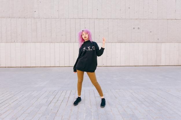 紫のアフロの髪とニューヨークスタイルの若い女性