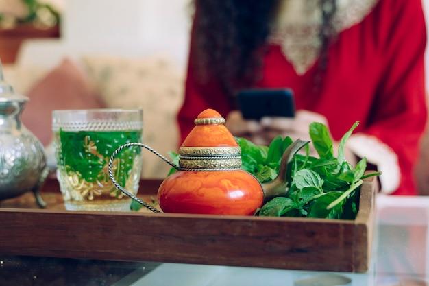 Деталь зеленого арабского чая на подносе и красивая молодая женщина, используя смартфон