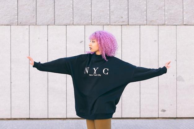 紫のアフロ髪とニューヨークのセーターの混血黒人女性