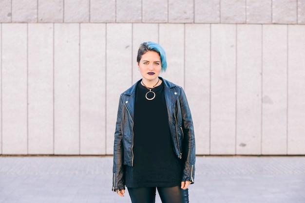 Молодая панк-женщина с синими волосами и кожаной курткой