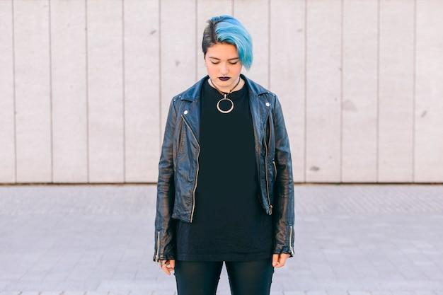Молодая панк-женщина с синими волосами и кожаной курткой смотрит вниз
