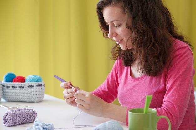 手作りのニット服を作成する若い進取的な女性