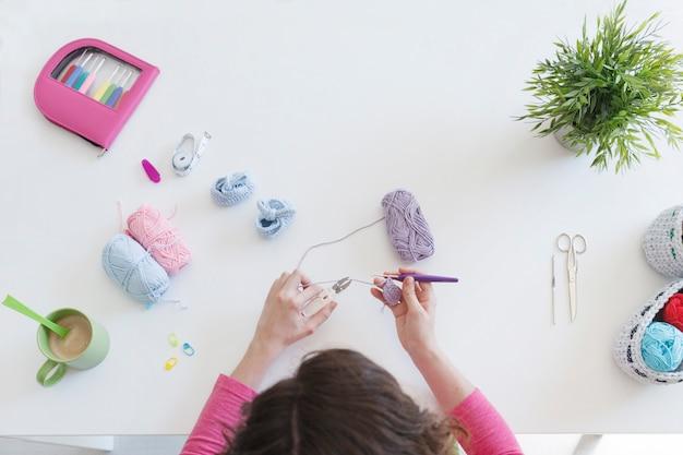 彼女のスタジオで男の赤ちゃんのブーティーを編む女性