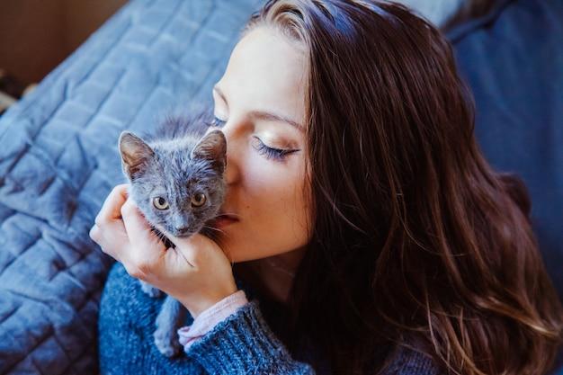 Молодая женщина целует котенка с нежной любовью.