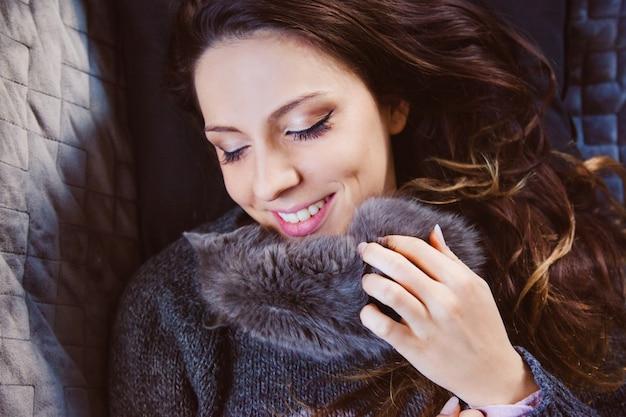 Взгляд сверху молодой женщины целуя и лаская котенка с нежной любовью.
