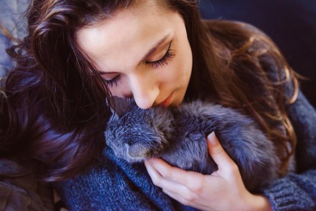 Деталь молодой женщины, целуя и лаская котенка с нежной любовью.