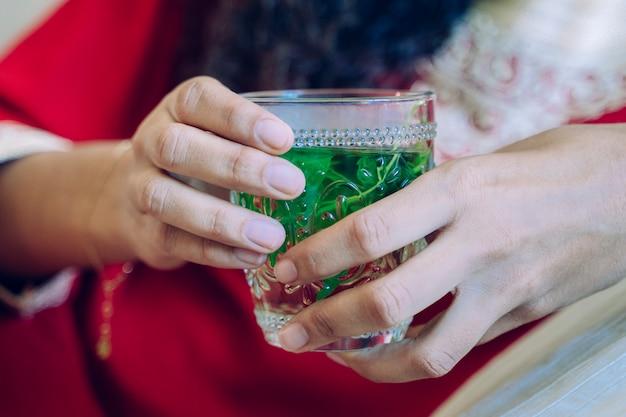 緑のアラブ茶を手で保持している女性