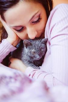 Молодая женщина целует котенка с нежной любовью. образ жизни любителей животных.