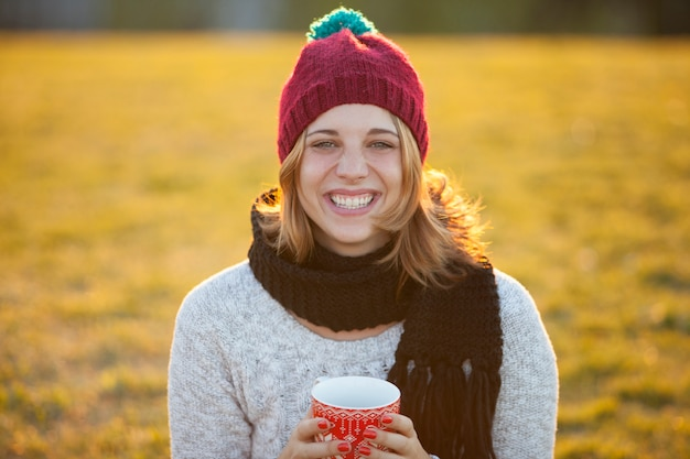 Жизнерадостная женщина в теплой шапке пьет кофе