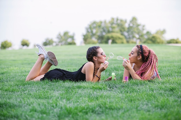公園で泡と遊ぶ若いガールフレンド